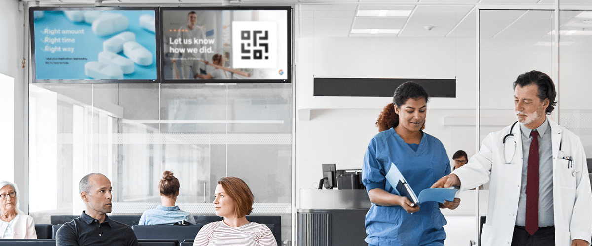 Doctor and nurse at a healthcare clinic with UPshow's signage on the waiting room TVs.