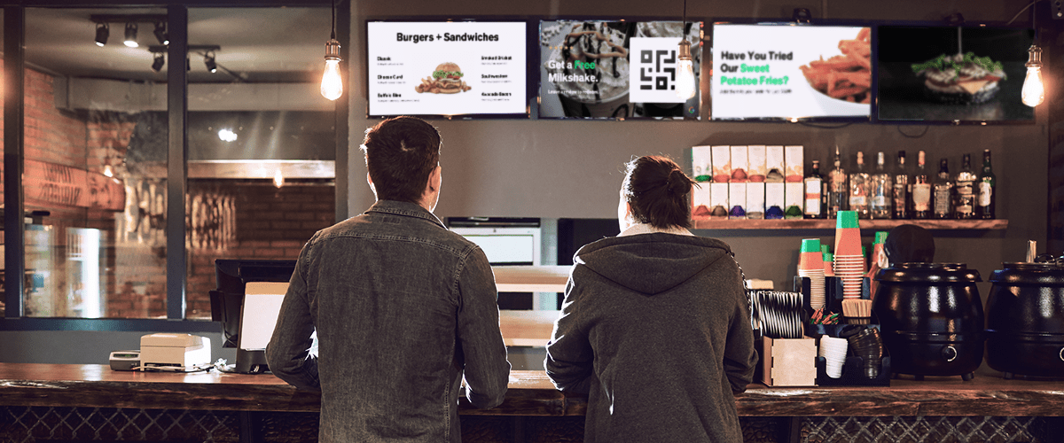 Two people at a restaurant with UPshow-driven food promotions on the screens behind the counter.